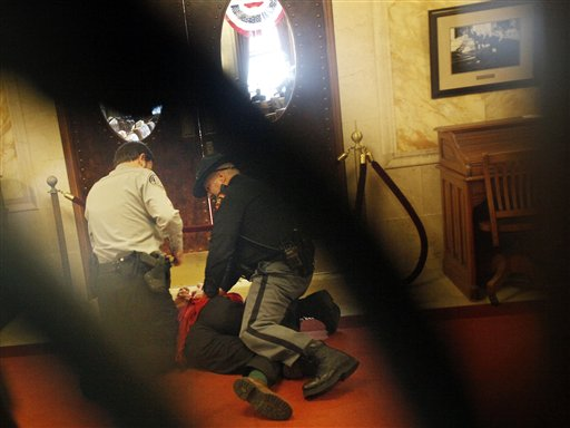 A protestor is handcuffed by law enforcement after he stormed the Assembly chamber doors at the Wisconsin Capitol building in Madison, Wis., Thursday, Feb. 17, 2011.