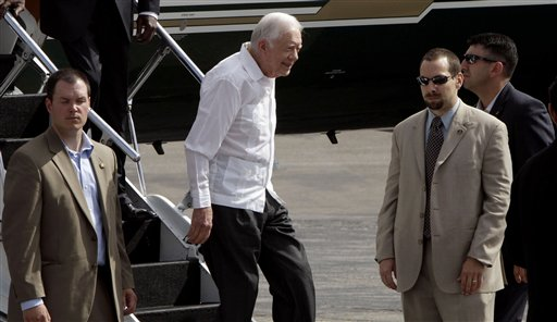 Former President Jimmy Carter, second from left, arrives to the Jose Marti airport in Havana, Cuba, Monday, March 29, 2011. Carter is in Cuba to discuss economic policies and ways to improve Washington-Havana relations, which are even more tense than usual over the imprisonment of a U.S. contractor on the island. (AP Photo/Franklin Reyes)