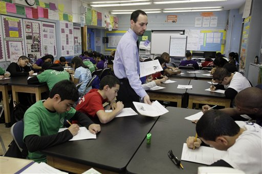 In a March 3, 2011 photo, teacher Josh Krinsky hands out materials in his Global History class the Washington Heights Expeditionary Learning School, in New York.  As Mayor Michael Bloomberg plans to take more than 6,000 teachers off the payroll to help balance a strained budget, some parent advocates are questioning what the layoffs will do to New York public school class sizes.  (AP Photo/Richard Drew)