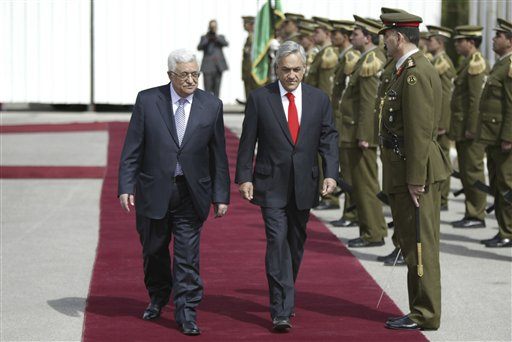 Palestinian President Mahmoud Abbas, left, and Chile's President Sebastian Pinera review an honor guard in the West Bank city of Ramallah, Saturday, March 5, 2011. Pinera is on a visit to Israel and the Palestinians. (AP Photo/Majdi Mohammed)