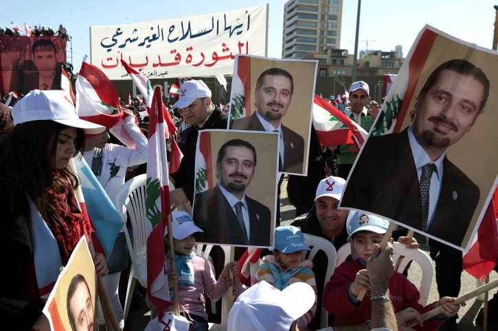 Lebanese supporters of March 14 movement carry placards showing the picture of Lebanese former Prime Minister Saad Hariri during a rally at Martyrs Square, in Beirut, Lebanon, 13 March 2011. Hundreds of Thousands of opposition supporters gathered to mark the sixth anniversary of a popular uprising against Syrian troops in Lebanon, demanding the disarming of Hezbollah.  EPA/NABIL MOUNZER