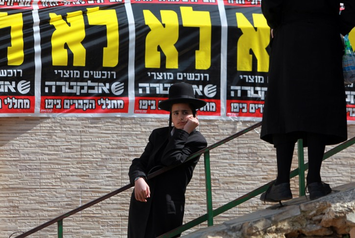 An ultra-Orthodox Jewish boy watches the crowd gather outside a 'yeshiva,' or seminary, in the Mea Shearim neighborhood of Jerusalem before a banner that reads, 'No ,NoNo, No' in Hebrew as a mass prayer is called to bury boxes of ancient bones on 28 March 2011. The bones were excavated from an archaeological site in Jaffa, south of Tel Aviv, over the past year and were the cause of protests and clashes with police over what the ultra-Orthodox say is the desercration of Jewish graves.  EPA/JIM HOLLANDER