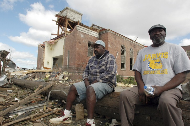 Sal Merritt, left, and Edrich Barnes rest outside the remains of Alberta Baptist Church in Tuscaloosa, Ala., on Thursday, April 28, 2011. The church was badly damaged by a tornado that left a path of destruction hundreds of yards wide. (AP Photo/Jay Reeves)