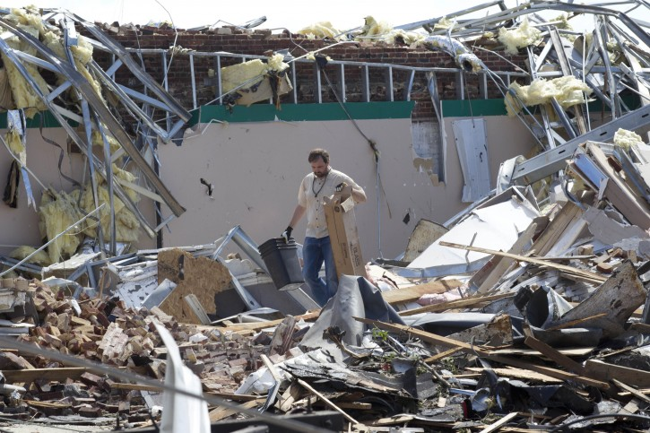Heath Meherg helps clean up his destroyed business in Cullman, Ala., Thursday, April 28, 2011. Dozens of tornadoes ripped through the South, flattening homes and businesses and killing at least 215 people in six states in the deadliest outbreak in nearly 40 years. (AP Photo/Dave Martin)