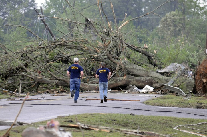 Concord Fire and Rescue personel run toward a large down tree that was blocking Warrior River Road after a tornado touched down, Wednesday, April 27, 2011 in Concord, Ala.  (AP Photo/Birmingham News, Jeff Roberts)