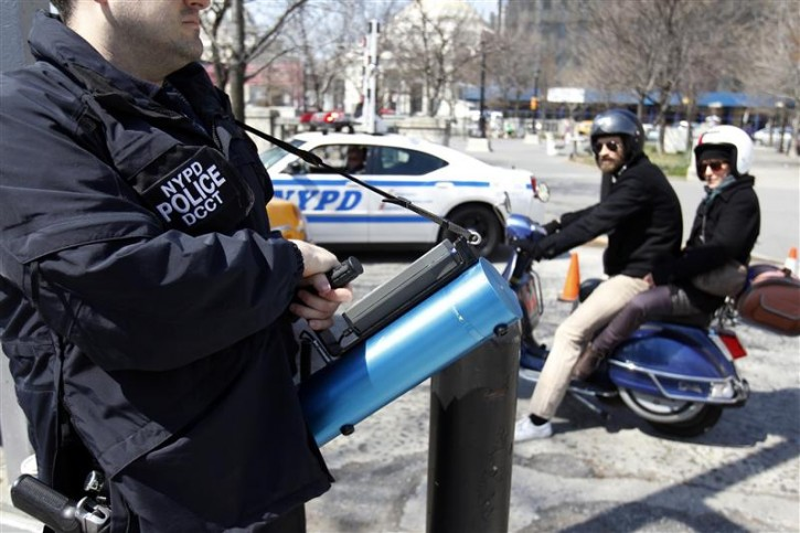 "A member of the NYPD holds a device used to detect levels of radiation as motorists pass by during a multi-agency ""dirty bomb"" exercise led by the New York Police Department in the Brooklyn section of New York April 9, 2011.  REUTERS/Jessica Rinaldi"
