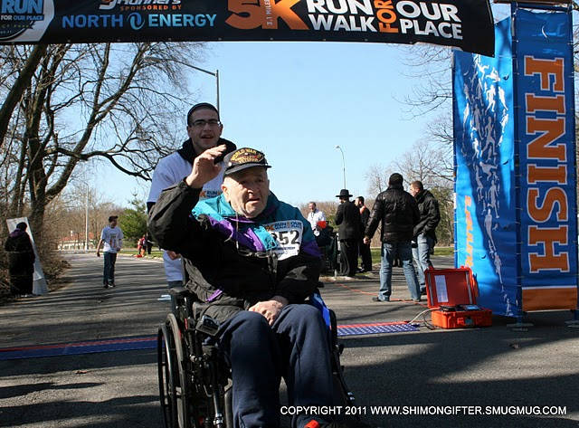 88 year old Avraham Silverman, a World War II veteran whose leg was recently amputated, completing the race in a wheelchair pushed by his grandson Aron Greenstein, who credits Our Place with saving his life.
