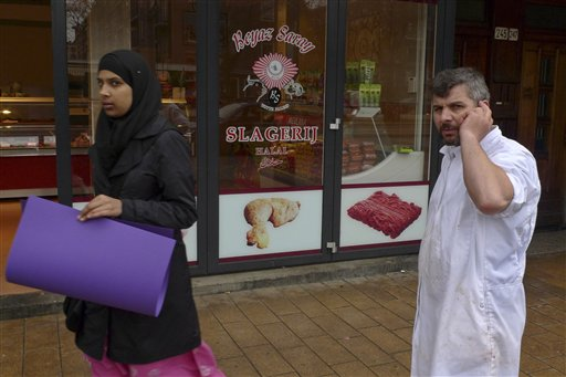 A butcher talks on his mobile phone as a veiled woman passes a Halal butchers store in Amsterdam, Netherlands, Thursday March 31, 2011. The Dutch parliament may soon pass a law banning centuries-old Jewish and Muslim traditions on the ritual slaughter of cows, sheep and chickens. If the Netherlands does outlaw procedures that make meat kosher for Jews or Halal for Muslims, it will be the first country outside of New Zealand to do so in recent years. (AP Photo/Peter Dejong)