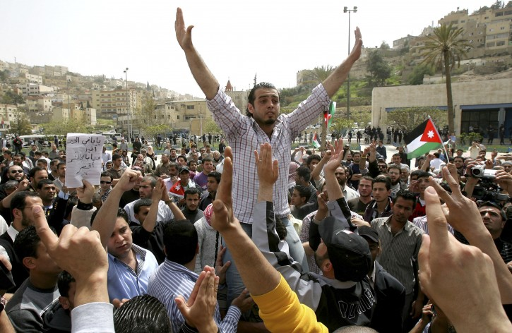 "A Jordanian pro-reform activist gestures during a rally outside the municipal offices in Amman, Jordan, Friday, April 1, 2011. About 400 pro-reform Jordanians turned out on Friday to demand more political say and demanding that the prime minister steps down. The Arabic on banner reads:""Seeker of good, come and seeker of evil, leave."" (AP Photo/Nader Daoud)"