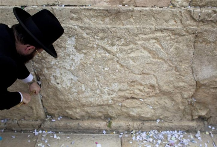 Western Wall Rabbi Shmuel Rabinovitz removes notes from the cracks of the Western Wall, Judaism's holiest prayer site, in Jerusalem's Old City April 6, 2011. As the Jewish holiday of Passover draws near, workers cleaned out the cracks and made room for more paper notes that Jews believe are notes to God. REUTERS/Darren Whiteside