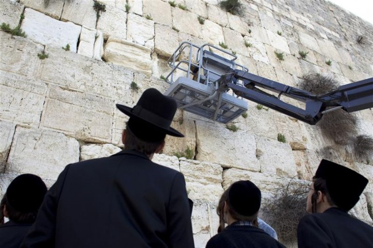 Ultra-Orthodox Jews watch as a worker checks the stones of the Western Wall, Judaism's holiest prayer site, in the Old City of Jerusalem April 6, 2011. As the Jewish holiday of Passover draws near, workers cleared notes out of the cracks and made room for more paper notes that Jews believe are notes to God. REUTERS/Darren Whiteside