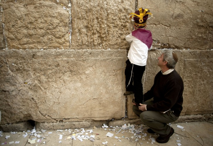 A boy removes prayer notes left by visitors from between the stones of the Western Wall, the holiest site where Jews can pray, in Jerusalem's Old City, Wednesday, April 6, 2011. The notes are buried in a nearby cemetery according to Jewish tradition. People of all faiths slip notes between the stones in the belief that god will answer their prayers. (AP Photo/Sebastian Scheiner)