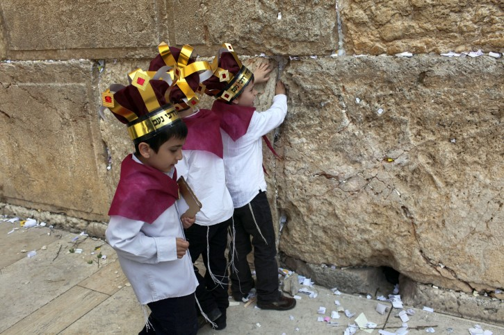 Young Jewish boys help in removing handwritten notes placed in the cracks between the large, ancient stones of the Western Wall, Judaism's holiest site, in the Old City of Jerusalem, Israel, 06 April 2011. Cleaning the thousands of notes from the Wall is an operation carried out with rabinical supervision twice a year, before Passover and the Jewish New Year holiday of Rosh Hashana. The notes are collected and given a Jewish burial on the Mount of Olives.  EPA/KOBI GIDEON