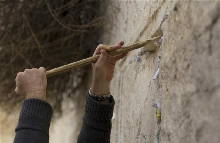 A worker removes notes from the cracks of the Western Wall, Judaism's holiest prayer site, in Jerusalem's Old City April 6, 2011. As the Jewish holiday of Passover draws near, workers cleaned out the cracks and made room for more paper notes that Jews believe are notes to God. REUTERS/Darren Whiteside