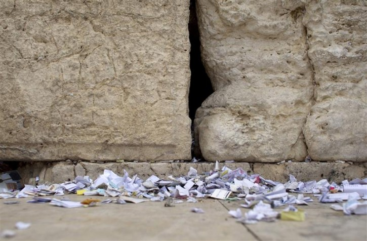 Notes are seen on the ground after they were removed from the cracks of the Western Wall, Judaism's holiest prayer site, in Jerusalem's Old City April 6, 2011. As the Jewish holiday of Passover draws near, workers cleaned out the cracks to make room for more paper notes that Jews believe are notes to God. REUTERS/Darren Whiteside