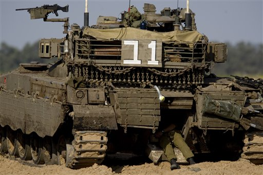 An Israeli soldier sits in a tank along the border between Israel and southern Gaza Strip, Saturday, April 9, 2011. Palestinian militants fired more than a dozen rockets at southern Israel on Saturday and Israeli warplanes killed four militants in the Gaza Strip in the most intense fighting since Israel's 2008-2009 offensive in the Hamas-ruled territory. (AP Photo/Ariel Schalit)