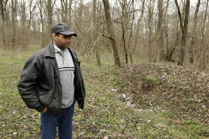 Villager Mihai Spanu walks by the former mass grave of dozens of Jews in a forest in Popricani village, near Iasi, 420 km (251 miles) north of Bucharest, April 4, 2011. Romania's Jewish community buried on Monday the remains of dozens of Jews killed by Romanian troops during World War Two and found in a mass grave in the north of the country. The memorial, dedicated to about 60 victims unearthed in a forest area near the village of Popricani, took place in the Jewish cemetery of Iasi in northeastern Romania. Archaeologists unearthed the mass grave in November 2010. REUTERS/Bogdan Cristel