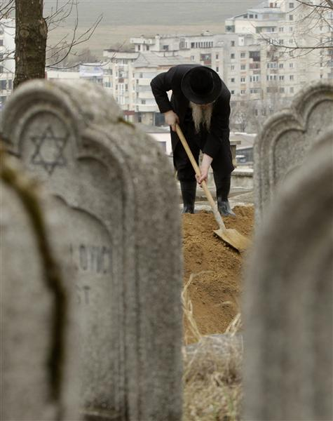 A Rabbi buries the remains of dozens of Jews in a cemetery in Iasi, 410 km (251 miles) north of Bucharest, April 4, 2011. Romania's Jewish community buried on Monday the remains of dozens of Jews killed by Romanian troops during World War Two and found in a mass grave in the north of the country. The memorial, dedicated to about 60 victims unearthed in a forest area near the village of Popricani, took place in the Jewish cemetery of Iasi in northeastern Romania. Archaeologists unearthed the mass grave in November 2010. REUTERS/Bogdan Cristel