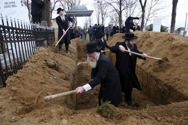Rabi Meir Sclesinger of London (front-L), accompanied by rabbis from England and the United States, takes part in the reburial of the remains of Holocaust victims, found in a mass grave in northern Romania, at the Jewish cemetery in Iasi, 410 km north of Bucharest, Romania, 04 April 2011. Romania's Jewish community buried the remains of dozens of Jews killed by Romanian troops during World War Two. The memorial is dedicated to about 60 victims unearthed in a forest near the village of Popricani. Archaeologists unearthed the mass grave in November 2010.  EPA/RADU ANECULAESI
