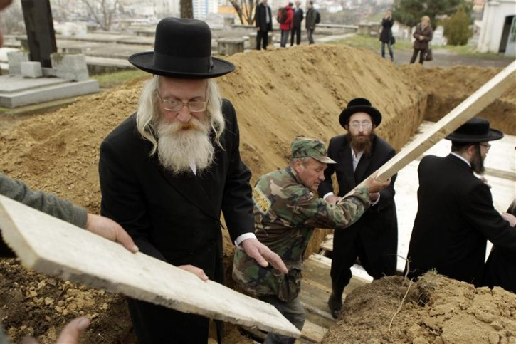 Rabbis from England and the United States prepare a grave to bury the remains of dozens of Jews in a cemetery in Iasi, 410 km north of Bucharest, April 4, 2011. Romania's Jewish community buried on Monday the remains of dozens of Jews killed by Romanian troops during World War Two and found in a mass grave in the north of the country. The memorial, dedicated to about 60 victims unearthed in a forest area near the village of Popricani, took place in the Jewish cemetery of Iasi in northeastern Romania. Archaeologists unearthed the mass grave in November 2010. REUTERS/Bogdan Cristel