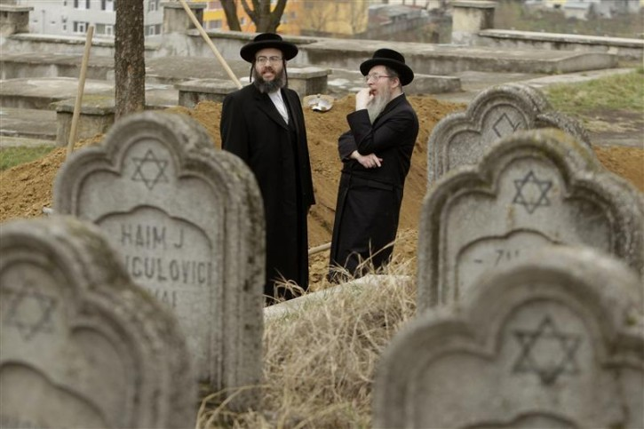 Rabbis from England and the United States are seen during the burial ceremony of the remains of dozens of Jews in a cemetery in Iasi, 410 km (251 miles) north of Bucharest, April 4, 2011. Romania's Jewish community buried on Monday the remains of dozens of Jews killed by Romanian troops during World War Two and found in a mass grave in the north of the country. The memorial, dedicated to about 60 victims unearthed in a forest area near the village of Popricani, took place in the Jewish cemetery of Iasi in northeastern Romania. Archaeologists unearthed the mass grave in November 2010. REUTERS/Bogdan Cristel