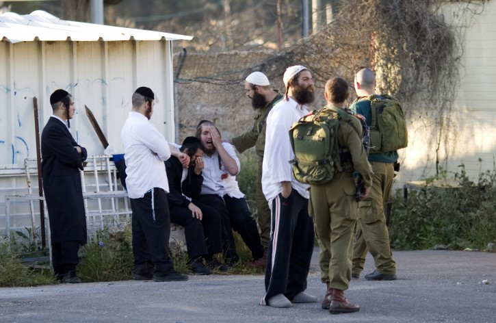 Jewish worshippers react moments after they arrived to at an entrance to a military base near the West Bank city of Nablus,  Sunday, April 24, 2011. Palestinians shot and killed one Israeli and wounded two others early Sunday near Joseph's Tomb, a Jewish holy site inside the Palestinian city of Nablus, the Israeli military and rescue services said. (AP Photo/Ariel Schalit)
