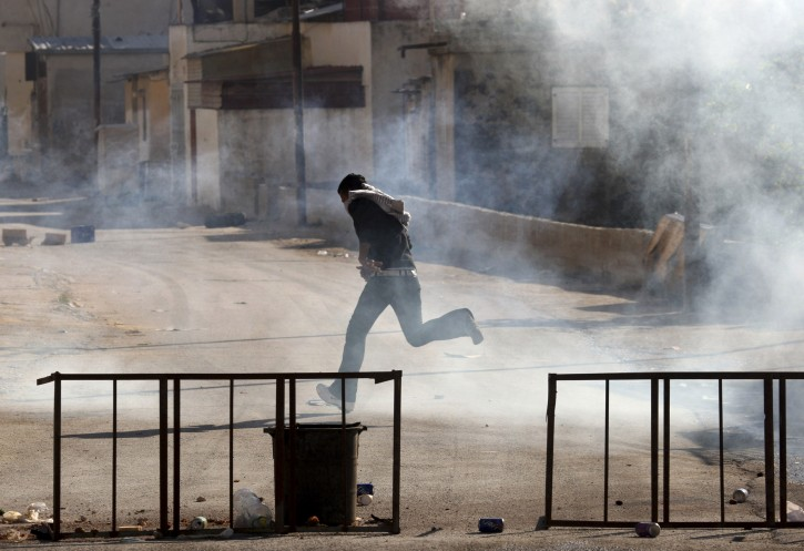 A Palestinian runs away from teargas fires by Israeli troops during clashes near Joseph's Tomb, in the West Bank city of Nablus, Sunday, April 24, 2011. Palestinians shot and killed one Israeli and wounded two others early Sunday near Joseph's Tomb, a Jewish holy site inside the Palestinian city of Nablus, the Israeli military and rescue services said.(AP Photo/Nasser Ishtayeh)