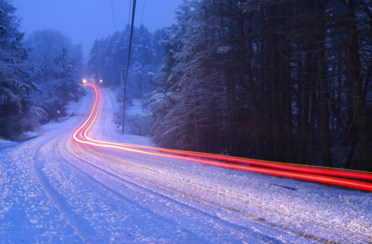 The tail lights of a car traveling down a road during a spring snowstorm leave a light trail in this 30-second time exposure in Freeport, Maine, Friday, April 1, 2011. (AP Photo/Robert F. Bukaty)
