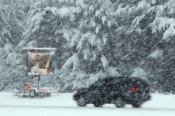 A motorist passes a sign urging drivers to reduce their speed to 45 mph during heavy snow fall on Interstate 295 in Freeport, Maine on Friday, April 1, 2011. (AP Photo/Robert F. Bukaty)