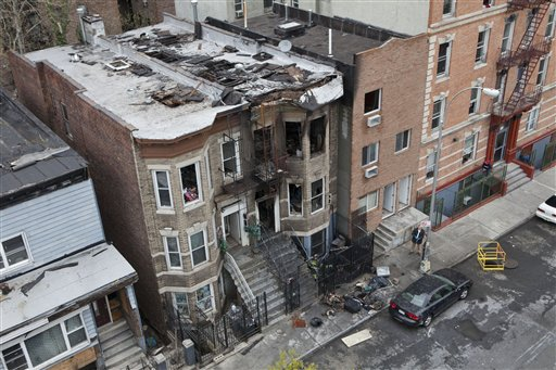 The scene of a house fire that killed three people is seen in the Bronx borough of New York on Monday, April 25, 2011. The fire killed a 36-year-old man, his 40-year-old wife and their 12-year-old son. (AP Photo/Andrew Burton)