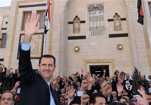 In this photo released by the Syrian official news agency SANA, Syrian President Bashar Assad, left, waves to his supporters after he made a speech at the Parliament, in Damascus, Syria, Wednesday, March 30, 2011. Syria's president has blamed the wave of protests against his authoritarian rule on 'conspirators' - but he failed to offer any concessions to appease the extraordinary wave of dissent. (AP Photo/SANA)
