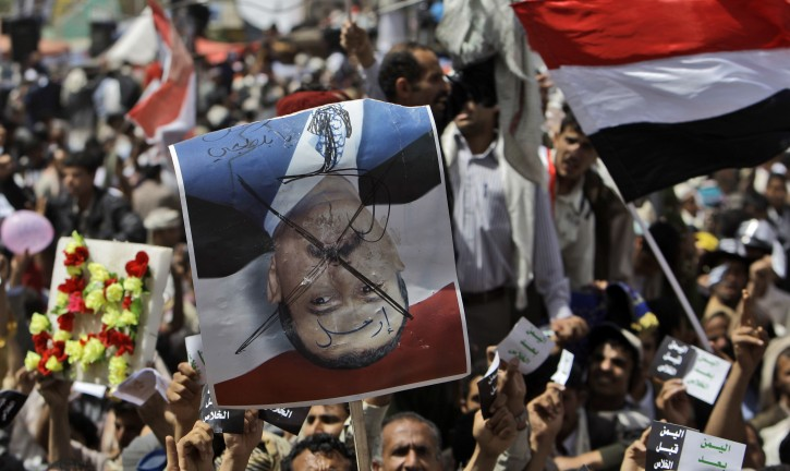 "An anti-government protestor holds up a defaced poster of Yemeni President Ali Abdullah Saleh that reads in Arabic "" Leave"", during a demonstration demanding the resignation of Yemeni President Ali Abdullah Saleh, in Sanaa,Yemen, Friday, April 1, 2011. Hundreds of thousands of Yemenis have packed a main square in the capital and are on the march elsewhere across the nation, demanding the country's ruler of 32 years step down. (AP Photo/Muhammed Muheisen)"