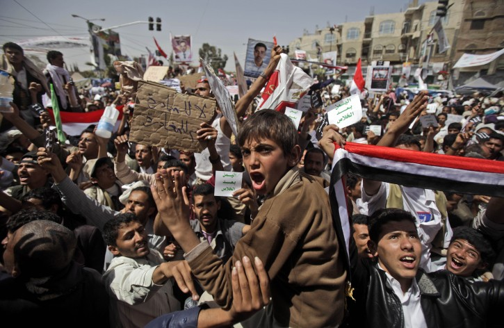 "Anti-government protestors react during a demonstration  demanding the resignation of Yemeni President Ali Abdullah Saleh, in Sanaa,Yemen, Friday, April 1, 2011. Hundreds of thousands of Yemenis have packed a main square in the capital and are on the march elsewhere across the nation, demanding the country's ruler of 32 years step down. Arabic reads on the banner left, "" No for the dialouge, yes for departure"". (AP Photo/Muhammed Muheisen)"
