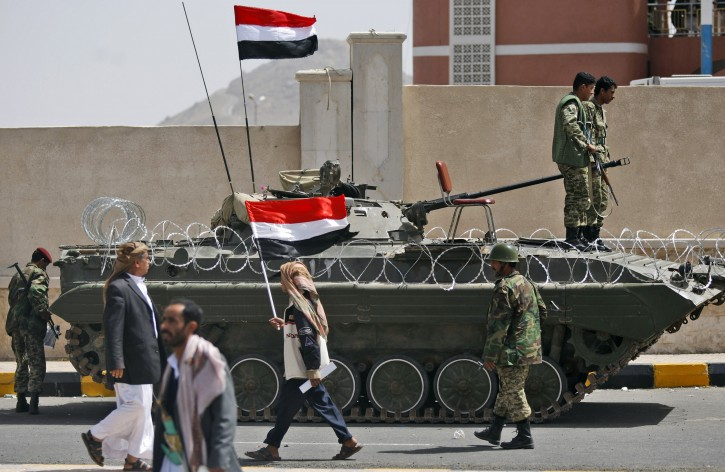 Supporters of Yemeni President Ali Abdullah Saleh walk by a tank following a rally supporting Saleh in Sanaa,Yemen, Friday, April 1, 2011. Hundreds of thousands of Yemenis have packed a main square in the capital and are on the march elsewhere across the nation, demanding the country's ruler of 32 years step down.  (AP Photo/Hani Mohammed)