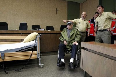 Sitting in a wheel chair former guard of the German Nazi death camp Sobibor, John 'Ivan' Demjanjuk (C), is brought into the court room of the state court in Munich, Germany, 05 May 2011. Demjanjuk is accused of the assistance of murder in 27,900 cases.  EPA/SEBASTIAN WIDMAN