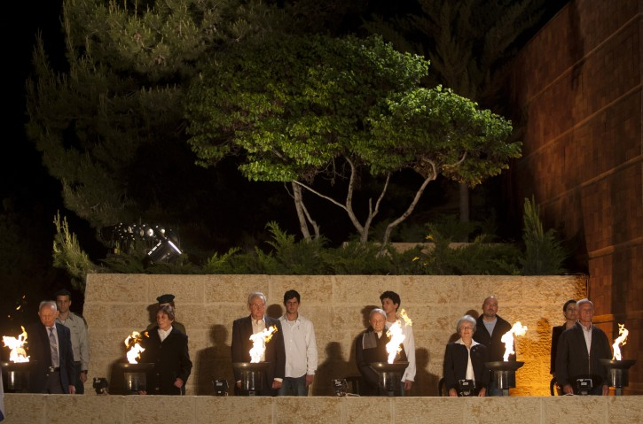 Holocaust survivors light six torches during the opening ceremony of Holocaust Remembrance Day at Yad Vashem Holocaust Memorial in Jerusalem, Sunday, May 1, 2011. The torches represent the six million victims of the Nazi genocide. (AP Photo/Sebastian Scheiner)