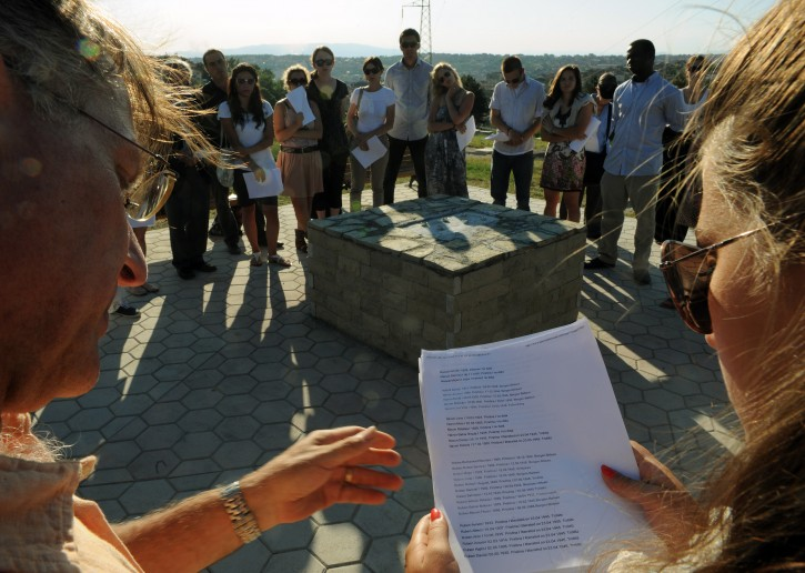Students of the Dartmouth College in New Hampshire, USA,  joined by students of the American University in Kosovo (AUK) read the names of Jewish families that perished during WWII  during a  dedication ceremony in the Jewish Cemetery in the capital Pristina on Thursday, June 23, 2011. AP