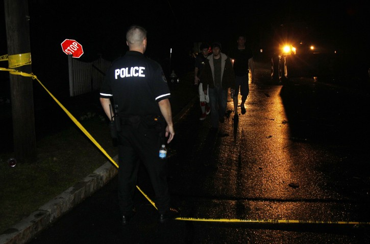 A police officer prevents pedestrians and vehicles  from going through a devastated area after a tornado swept through Monson, Mass. Wednesday, June 1, 2011. (AP Photo/Elise Amendola)