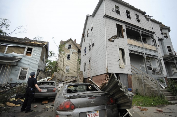 A police officer checks on people in a house after a reported tornado struck Springfield, Mass., Wednesday, June 1, 2011. An apparent tornado struck downtown Springfield, one of Massachusetts' largest cities, scattering debris, toppling trees, and frightening workers and residents. (AP Photo/Jessica Hill)