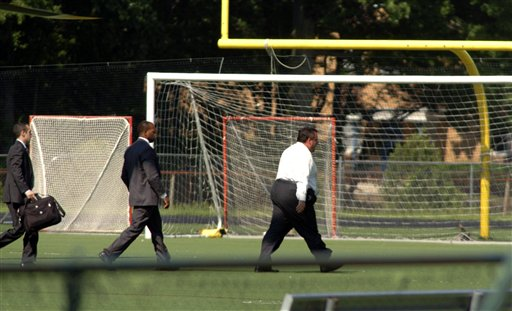 In this May 31, 2011 photo, New Jersey Gov. Chris Christie, right, walks toward playing fields after exiting a state helicopter to attend his son's high school baseball game in Montvale, N.J. State police say it costs $2,500 an hour to fly a state helicopter, but that flying Christie to his son's high school baseball game didn't cost taxpayers anything extra. (AP Photo/PATCH.com, Christopher Costa) MANDATORY CREDIT