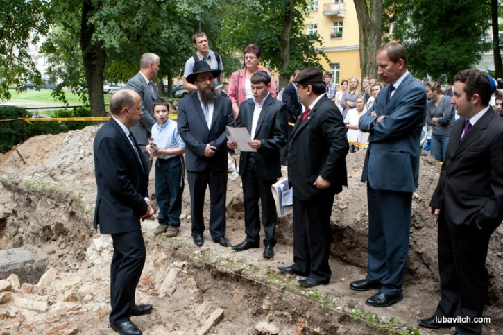 Lithuanian Prime Minister Andrius Kubilius (left) looks on as a student from Beis Menachem recites a prayer. At the student's right is MP Emmanuel Zingeris who inspired the excavation. At his left is Chabad-Lubavitch representative to Lithuania, Rabbi Sholom Ber Krinsky