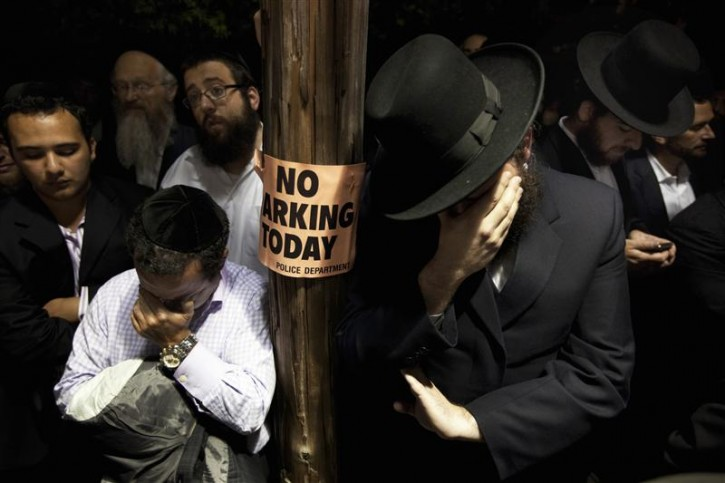 Men weep while listening to the funeral of Leibby Kletzky outside a synagogue in the Brooklyn borough of New York July 13, 2011. A Brooklyn man was under arrest on Wednesday after the dismembered remains of Kletzky, who had gotten lost two days earlier walking home from camp, were found in the man's freezer and a trash container, police said. Kletzky, 8, was supposed to meet his family on Monday on his walk home from day camp in Brooklyn's Borough Park neighborhood but never arrived, police said.  REUTERS/Lucas Jackson