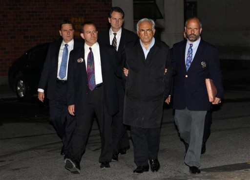 AP File - Doing the perp walk, Dominique Strauss-Kahn (2nd R), head of the International Monetary Fund (IMF), departs a New York Police Department precinct in New York late May 15, 2011.