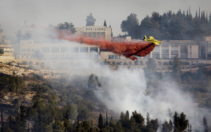 A fire plane drops red fire retardant to try to extinguish fires burning in the forest below Yad Vashem Holocaust memorial, seen in background, in Jerusalem Sunday, July 17, 2011. An out of control wildfire has forced the evacuation of Israel's Holocaust memorial Yad Vashem. (AP Photo/Ben Curtis)