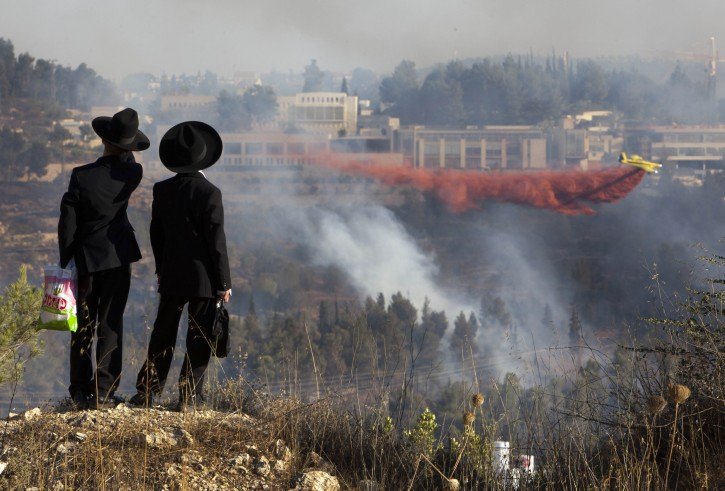Ultra-Orthodox Jewish boys watch from an opposite hill as a fire plane drops red fire retardant to try to extinguish fires burning in the forest below Yad Vashem Holocaust memorial, seen in background, in Jerusalem Sunday, July 17, 2011. An out of control wildfire has forced the evacuation of Israel's Holocaust memorial Yad Vashem. (AP Photo/Oded Balilty)