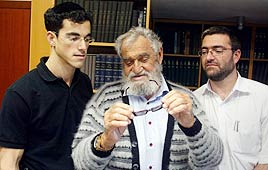 Rabbi Halperin (c) looking at a pair of glasses. (left) his Son Dovid, and Yaakov (right