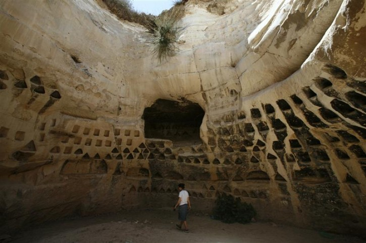 A tourist walks inside a columbarium at Hirbet Madras archaeological site, featuring ancient rebel hideouts, at the foothills of Jerusalem around the ancient city of Beit Guvrin August 23, 2011. You'll need a headlamp, a tight waistline and no fear of the dark in order to enjoy one of the most extreme, yet lesser known, archaeological wonders of the Holy Land - Ancient tunnel systems dug by Jewish rebels to fight the Roman empire. Picture taken August 23, 2011. To match Reuters Life! ISRAEL-CAVES/  REUTERS/Baz Ratner