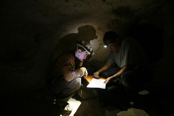 Researchers Boaz Langford (L) and Boaz Zissu kneel inside an ancient rebel hideout at Hurvat Burgin archaeological site, at the foothills of Jerusalem around the ancient city of Beit Guvrin August 30, 2011. You'll need a headlamp, a tight waistline and no fear of the dark in order to enjoy one of the most extreme, yet lesser known, archaeological wonders of the Holy Land - the ancient tunnel systems dug by Jewish rebels to fight the Roman empire. To match Reuters Life! ISRAEL-CAVES/  REUTERS/Baz Ratner