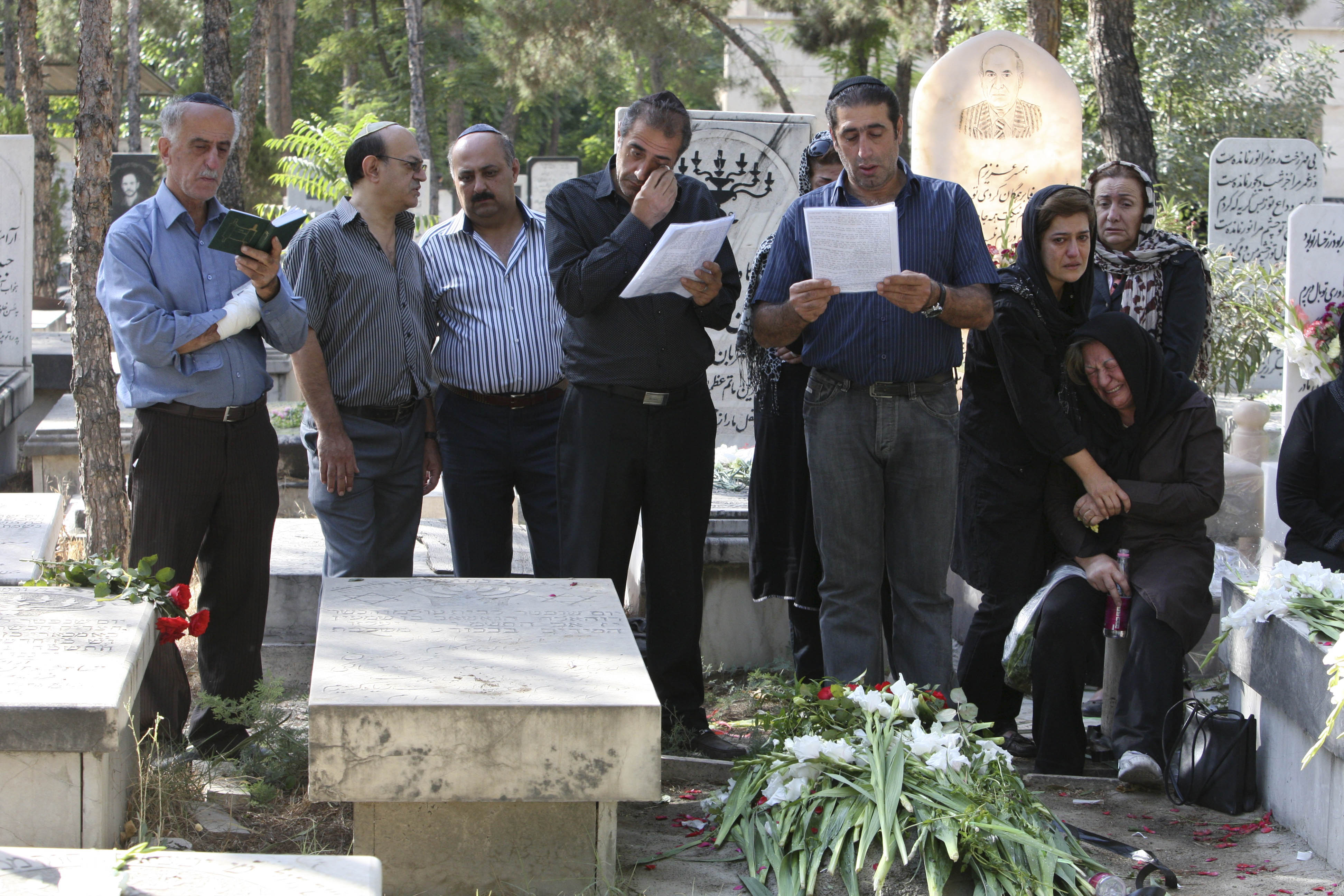Tehran iran in photos annual memorial day held at iranian jewish iranian jews pray and mourn at the grave of their loved one covered with flowers izmirmasajfo Gallery