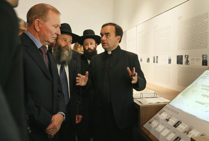 French Catholic Priest Patrick Desbois, right, presenting his exhibition 'Shoah by Bullets: Mass shootings of Jews in Ukraine 1941-1944' to former Ukrainian President Leonid Kuchma, left, in Kiev, Ukraine,  Thursday, Sept. 8, 2011. An exhibition devoted to the Nazi massacre of 1.4 million Jews in Soviet Ukraine during the Holocaust has opened in Kiev. The exhibit is based on the work of French Catholic Priest Patrick Desbois who has been canvassing the towns and villages of Ukraine to search for Jewish mass graves and interview the elderly witnesses to the Holocaust.  (AP Photo/Efrem Lukatsky)
